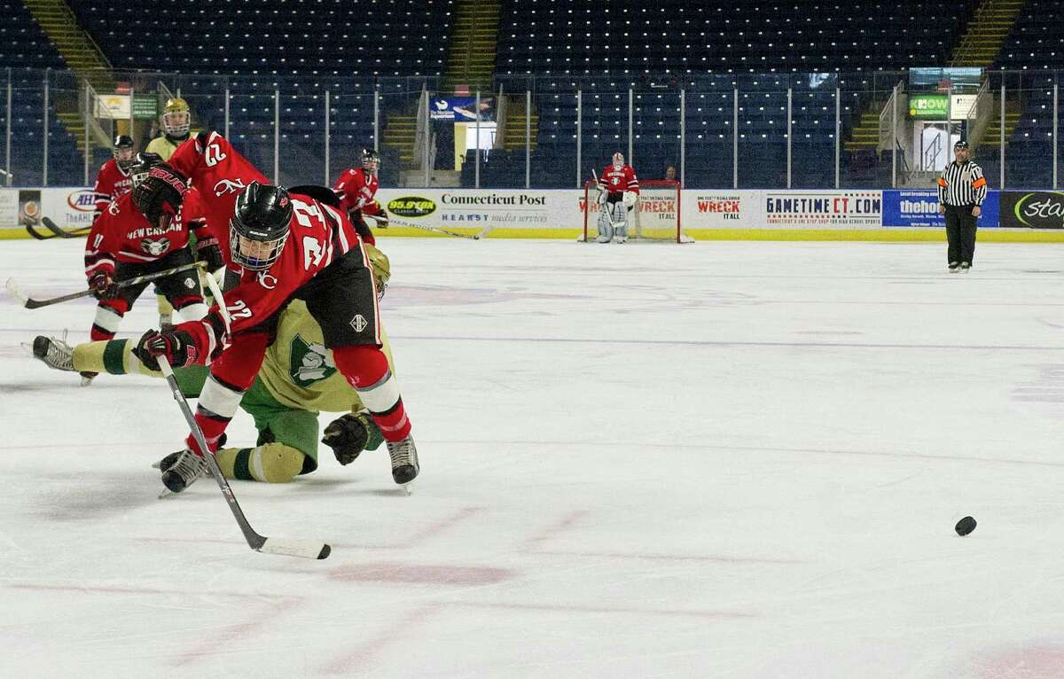 New Canaan's Patrick Hompe loses his footing while attempting to take a shot during Saturday's Division I semifinal game at Webster Bank Arena in Bridgeport, Conn., on March 15, 2014.