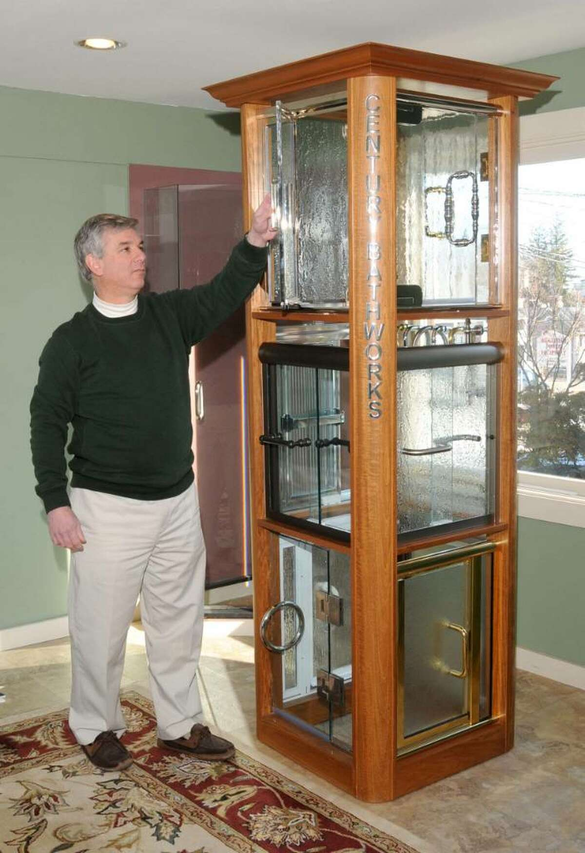 John Petchonka, co-owner of Ridgefield Glass, shows shower enclousure choices from the frame shower display,in the company's showroom at 4 Danbury Rd., Ridgefield, CT, on Tuesday, Feb.9, 2010
