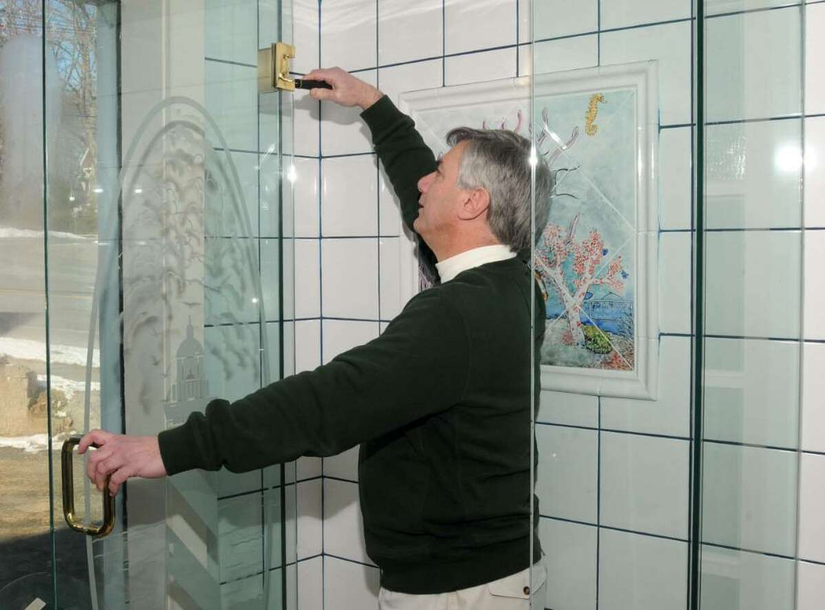 John Petchonka, co-owner of Ridgefield Glass, adjust the door of a glass shower enclousure, in the company's showroom at 4 Danbury Rd., Ridgefield, CT, on Tuesday, Feb.9, 2010