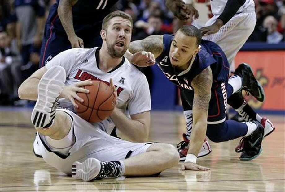 Louisville forward Stephan  Van Treese, left, tries to pass the ball away as Connecticut guard  Shabazz Napier, right, closes in during the first half of an NCAA  college basketball game in the finals of the American Athletic  Conference men's tournament Saturday, March 15, 2014, in Memphis, Tenn.  (AP Photo/Mark Humphrey)