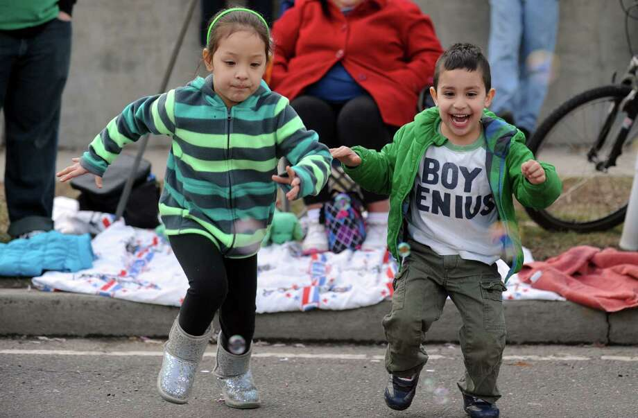 Siblings Emily Roos, 5, and Sam Nieves, 4, race to get candy during the annual St. Patrick's Day Parade in downtown Milford, Conn. Saturday, Mar. 15, 2014. Photo: Autumn Driscoll / Connecticut Post