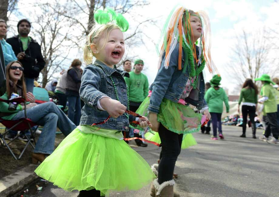 Four-year-old Lyla Mueller, of Naugatuck, waves to marchers with her sister Angelena, 8, during the annual St. Patrick's Day Parade in downtown Milford, Conn. Saturday, Mar. 15, 2014. Photo: Autumn Driscoll / Connecticut Post