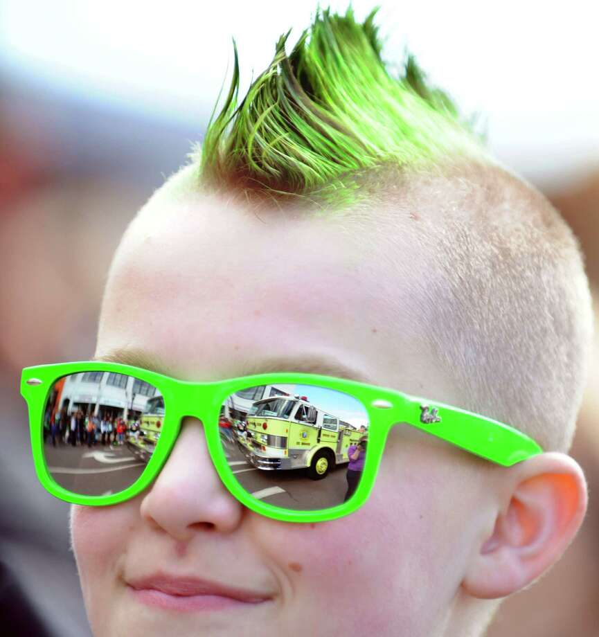 Firetrucks reflect in 14-year-old Logan Herb's sunglasses as the St. Patrick's Day Parade moves through downtown Milford, Conn. Saturday, Mar. 15, 2014. Photo: Autumn Driscoll / Connecticut Post