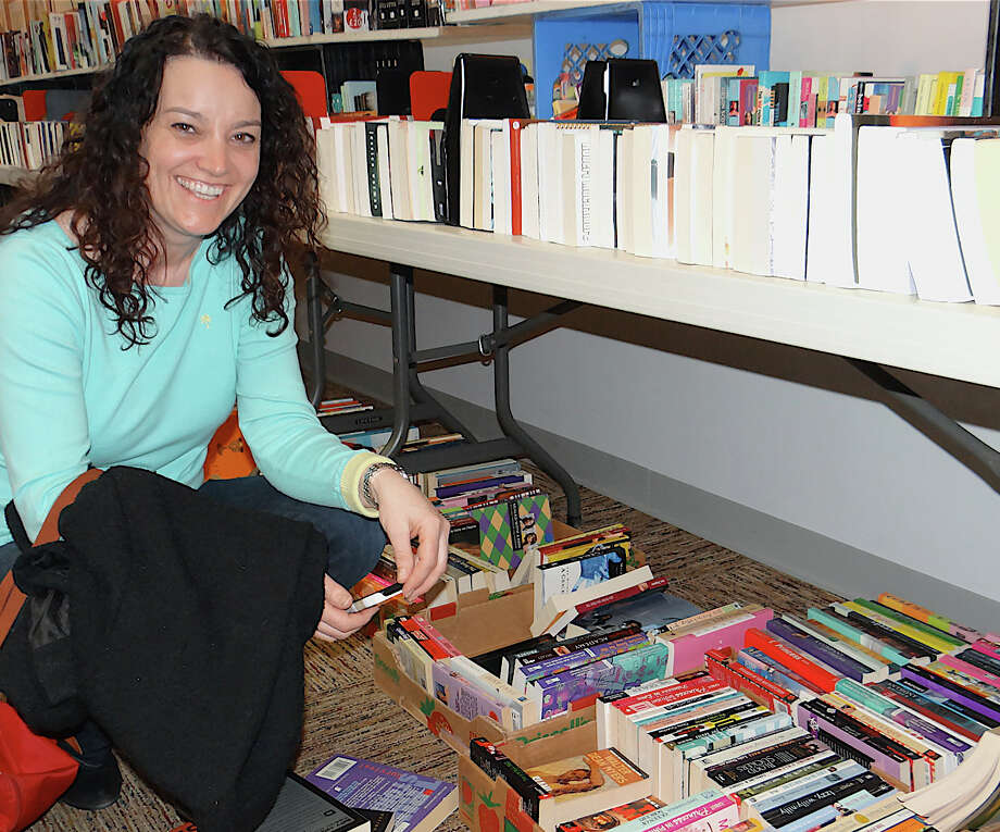 Tricia Farnworth of Westport looks through inventory on the opening day Saturday of the Westport Public Library's March Book Sale. Photo: Mike Lauterborn / Westport News