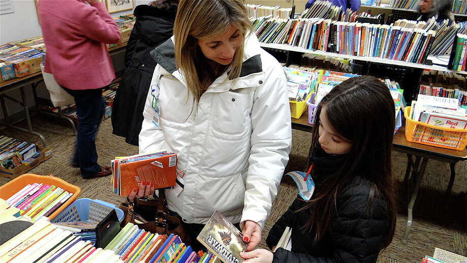 Deborah Markus of Westport and daughter, Maya, 9, look at children's books at the Westport Library's March Book Sale. Photo: Mike Lauterborn / Westport News