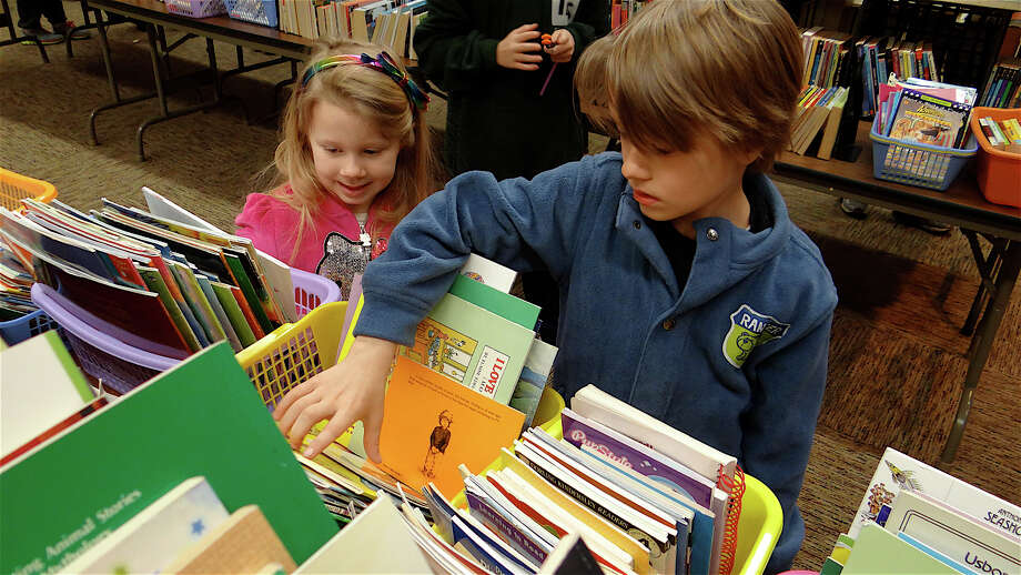 Jocelyn Files, 5, of Stratford and her brother, Xander, 7, look through children's books at the Westport Library's March Book Sale. Photo: Mike Lauterborn / Westport News