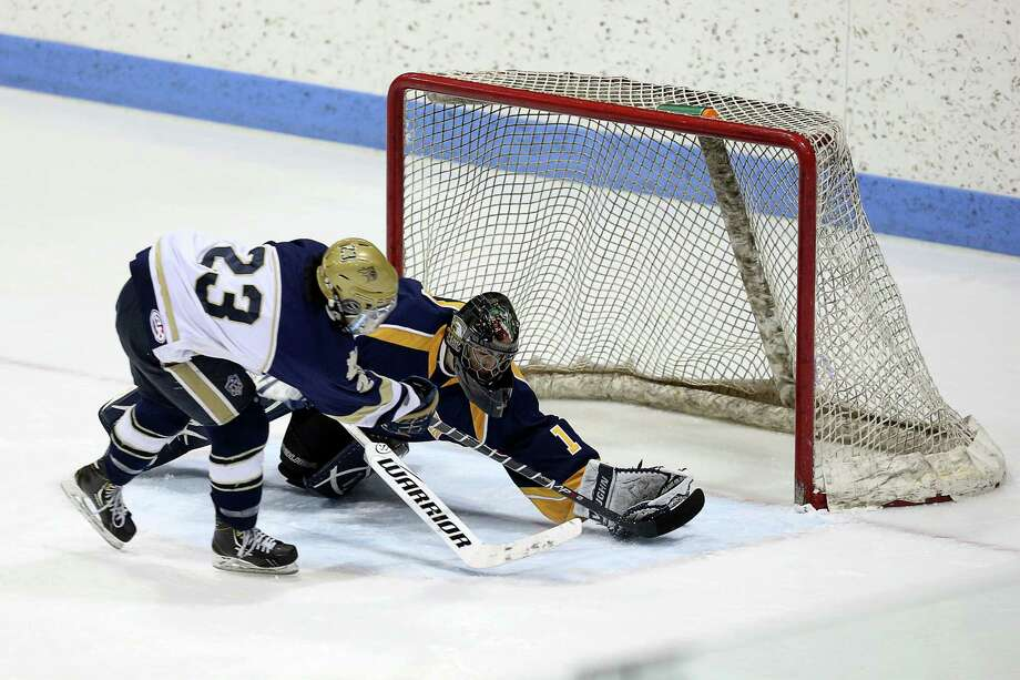 Notre Dame of Fairfield's #23 Jonny Suporn makes a goal over East Haven High School's #1 Tom DeLucia during Saturday evening CIAC State Tournament at Ingallis Rink in New Haven. Photo: Mike Ross / Mike Ross Connecticut Post freelance -www.mikerossphoto.com