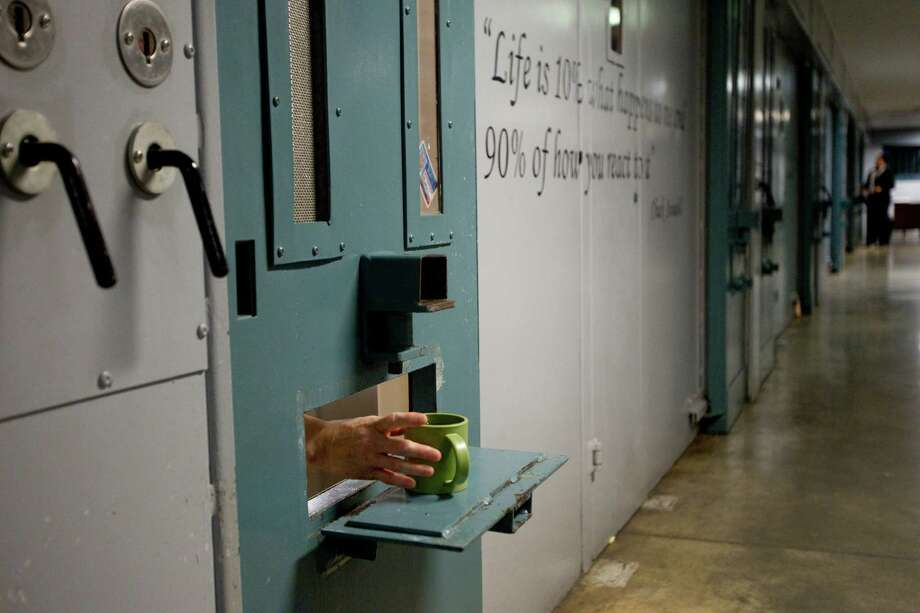 An inmate reaches out for his cup in the administrative segregation wing of the Estelle Unit last year in Huntsville. Photo: Brett Coomer, Staff / © 2014 Houston Chronicle