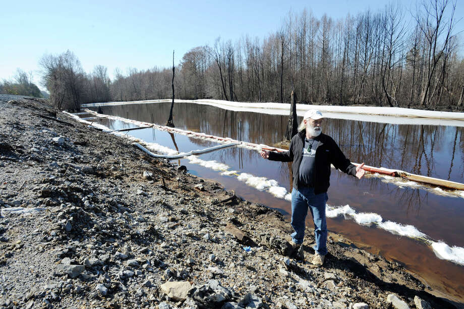 John Wathen, an environmentalist with the Waterkeeper Alliance, gestures at the site of a train derailment and oil spill near Aliceville, Ala., on Wednesday, May 5, 2014. Environmental regultors say cleanup and containment work is continuing at the site, but critics contend the accident and others show the danger of transporting large amounts of oil in tanker trains. (AP Photo/Jay Reeves) ORG XMIT: ALJR201 Photo: Jay Reeves / AP