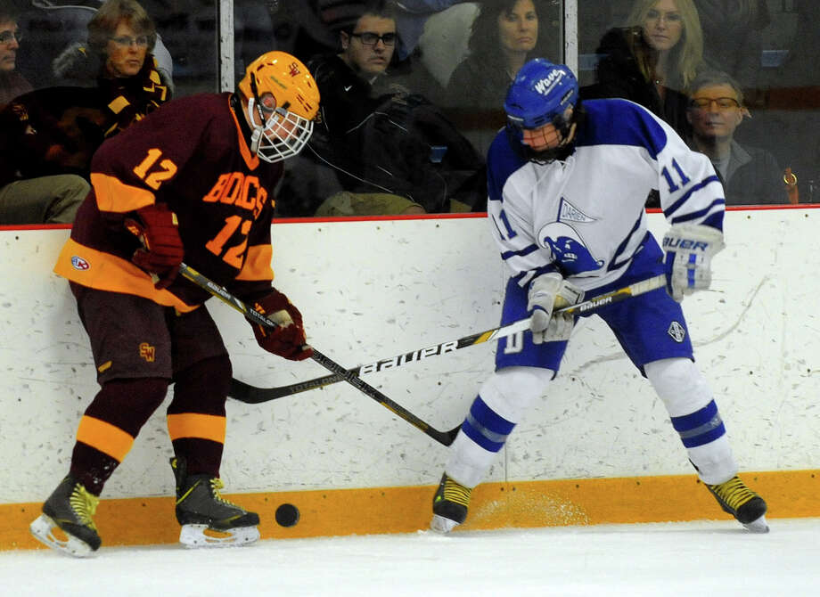 Darien's Nicholas Tuzinkiewicz, right, and South Windsor's Patrick Lawson converge on the puck, during Division I state quarterfinal hockey action in West Haven, Conn. on Saturday March 15, 2014. Photo: Christian Abraham / Connecticut Post