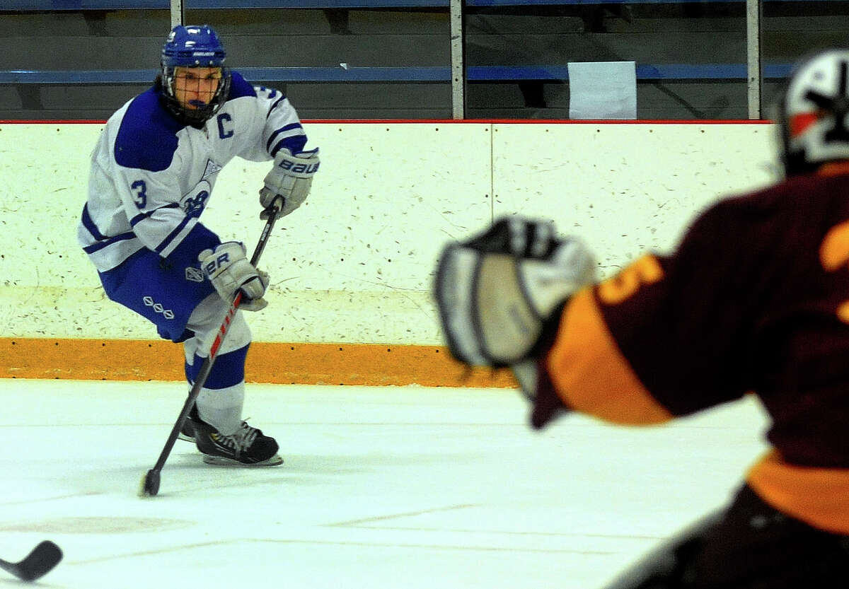 Darien's Thomas Watters drives towards the goal, during Division I state quarterfinal hockey action against South Windsor in West Haven, Conn. on Saturday March 15, 2014. Guarding the goal is South Windsor's Scott Skenyon.
