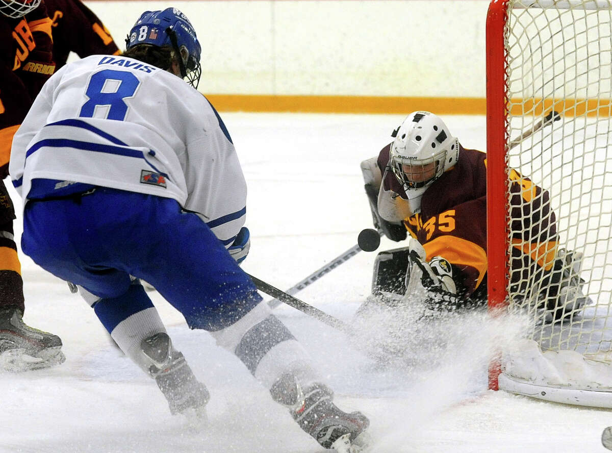Darien's Connor Davis tries to reach the puck at the goal, during Division I state quarterfinal hockey action against South Windsor in West Haven, Conn. on Saturday March 15, 2014. Guarding the goal is South Windsor's Scott Skenyon.