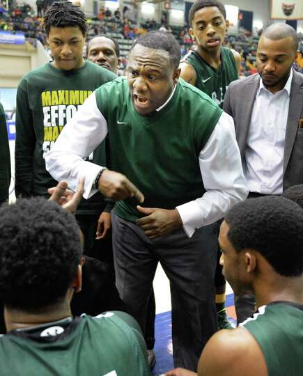 Green Tech head coach Jamil Hood, Sr., center, with players during a time out in the Class AA boys'