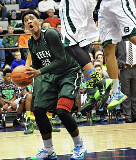 Green Tech's #35 Ramion Burt, leftt, moves under Brentwood defenders in the Class AA boys' basketbal