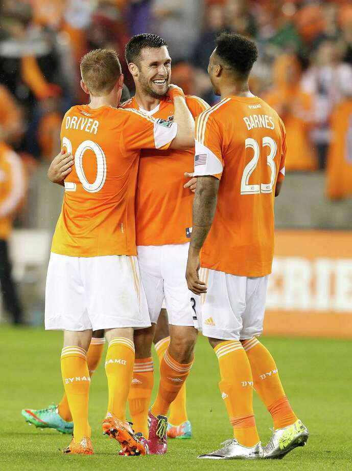 3/15/14: Houston Dynamo forward Will Bruin (12) is congratulated by Houston Dynamo midfielder Andrew Driver (20) and Houston Dynamo midfielder Giles Barnes (23) in the first half at BBVA Compass Stadium in Houston, Texas. Photo: Thomas B. Shea, For The Chronicle / © 2014 Thomas B. Shea