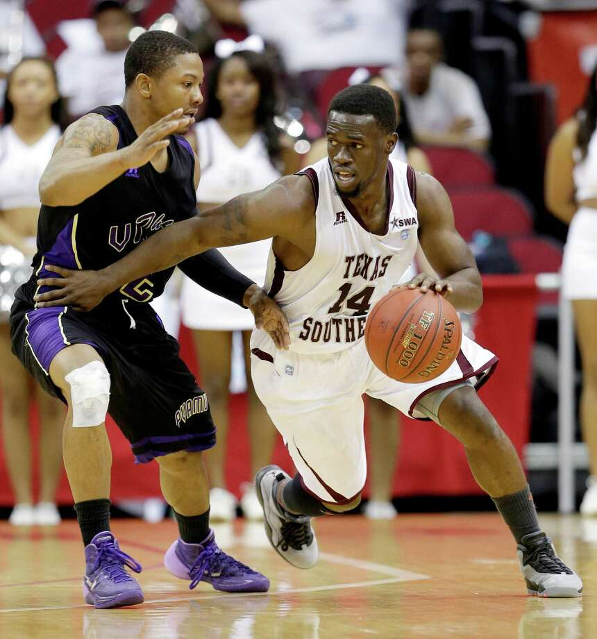 Texas Southern's Ray Penn (14) drives around Prairie View A&M's John Brisco during the second half of an NCAA college basketball game in the championship of the Southwestern Athletic Conference tournament Saturday, March 15, 2014, in Houston. Texas Southern won 78-73. (AP Photo/David J. Phillip) Photo: David J. Phillip, Associated Press / AP