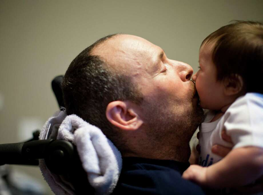 Captain Bill Dowling gives a kiss to his friend's three-month-old son Ryan Rainville, Friday, March 14, 2014, in Tomball. Dowling receives friends and colleagues to this home in Tomball everyday. Photo: Marie D. De Jesus, Houston Chronicle / © 2014 Houston Chronicle