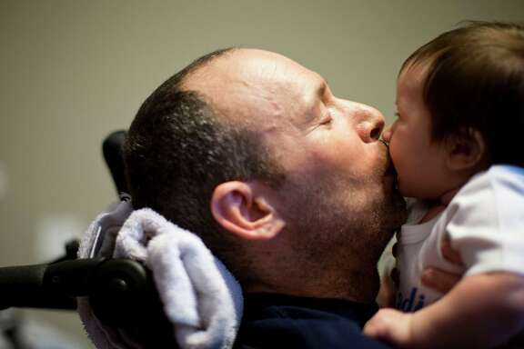 Captain Bill Dowling gives a kiss to his friend's three-month-old son Ryan Rainville, Friday, March 14, 2014, in Tomball. Dowling receives friends and colleagues to this home in Tomball everyday.