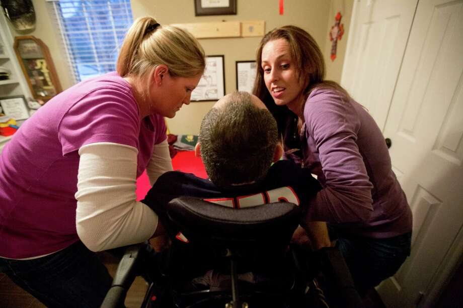Bill Dowling's sister, Mary Harrison, right, and a close family friend Courtney Rainville, left, help Dowling sit back on his wheelchair after over an hour of rehabilitation therapy, Friday, March 14, 2014, in Tomball. Photo: Marie D. De Jesus, Houston Chronicle / © 2014 Houston Chronicle