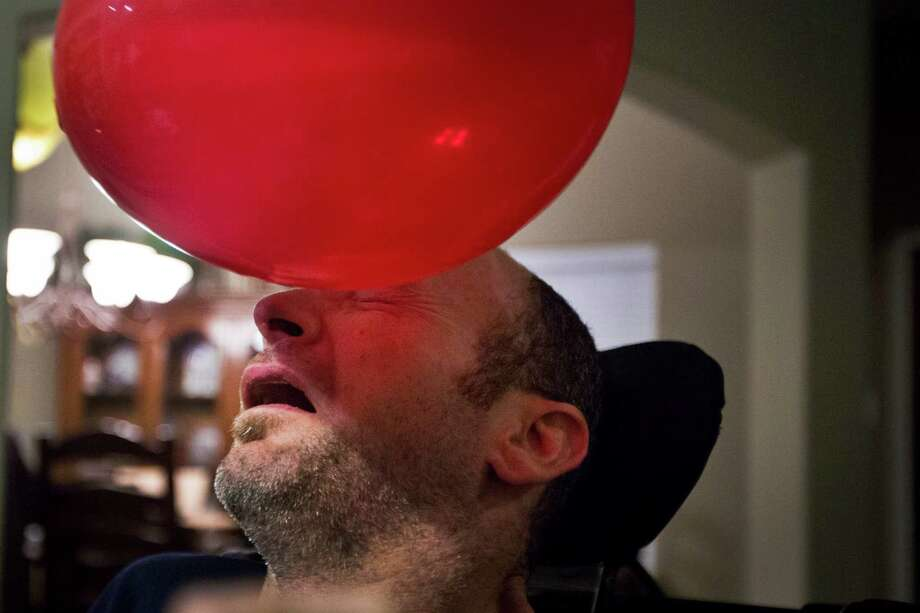 Bill Dowling goofs around with one of his birthday balloons during a family get-together, Friday, March 14, 2014, in Tomball. Photo: Marie D. De Jesus, Houston Chronicle / © 2014 Houston Chronicle