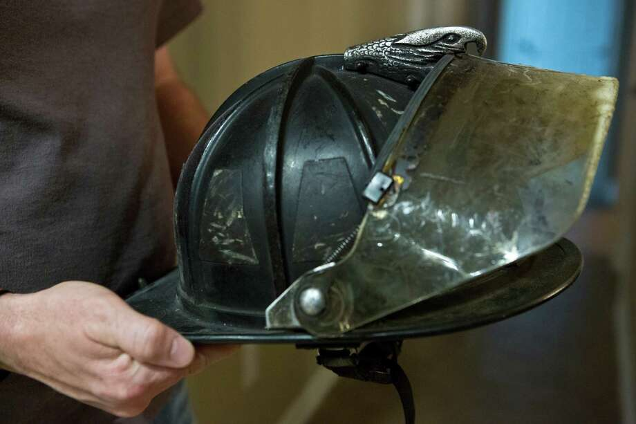 John Dowling, Captain Bill Dowling's brother holds the helmet the captain used during the motel fire that caused serious injuries to Bill Dowling, including the loss of both his legs. Friday, March 14, 2014, in Tomball. Photo: Marie D. De Jesus, Houston Chronicle / © 2014 Houston Chronicle