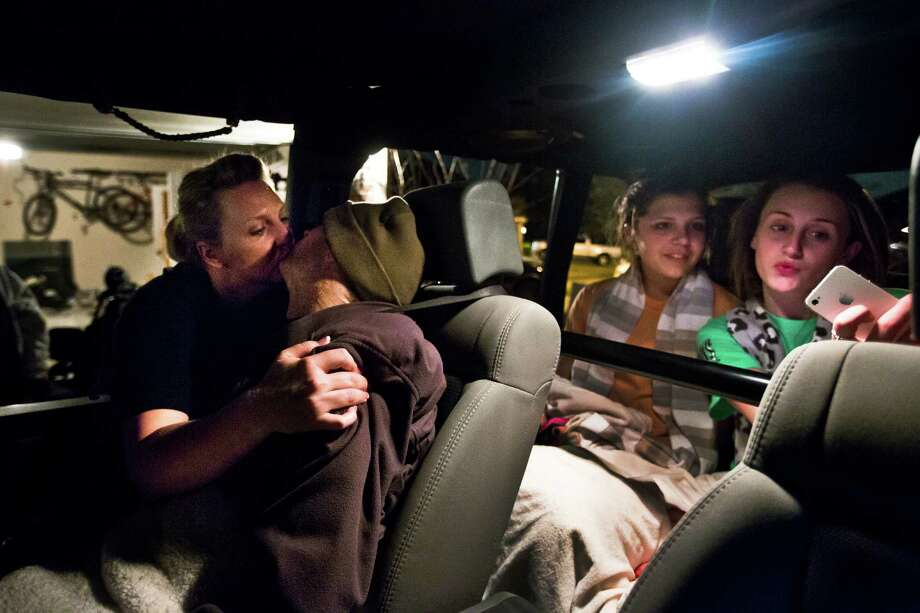 Jacki Dowling, left, kisses her husband who is leaving with his daughter Faith Dowling and a family friend Cramer Townsley for an evening drive, Friday, March 14, 2014, in Tomball. Photo: Marie D. De Jesus, Houston Chronicle / © 2014 Houston Chronicle
