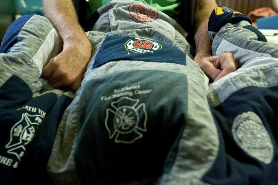 Captain Bill Dowling's hands rest on top of a lap quilt made with t-shirts from different fire departments that were gifted as a caring gesture to him and his family. Saturday, March 15, 2014, in Tomball. Photo: Marie D. De Jesus, Houston Chronicle / © 2014 Houston Chronicle