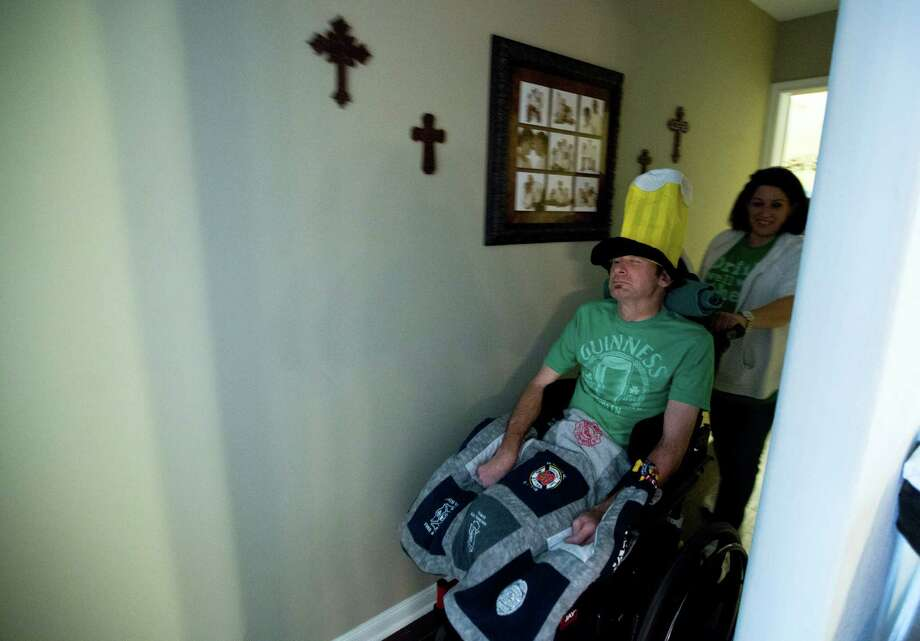 Theda Pyle wheels Bill Dowling out of his room after getting him ready for the 2014 St. Patricks Parade in Houston, Saturday, March 15, 2014. Photo: Marie D. De Jesus, Houston Chronicle / © 2014 Houston Chronicle
