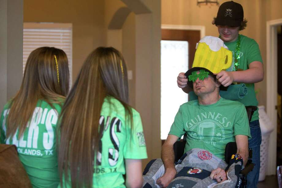 Foster Dowling, 12, covers his dad's head with a beer motive hat as part of the preparations to go to the 55th Annual Houston St. Patrick's Parade, Saturday, March 15, 2014, in Houston. Dowling is this year's parade grand marshal. Photo: Marie D. De Jesus, Houston Chronicle / © 2014 Houston Chronicle