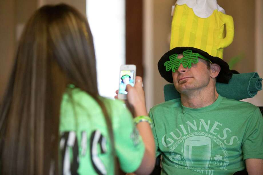 Faith Dowling takes an iPhone photo of her dad Captain Bill Dowling with a beer hat before heading to the 2014 St. Patrick's Parade, Saturday, March 15, 2014, in Houston. Photo: Marie D. De Jesus, Houston Chronicle / © 2014 Houston Chronicle