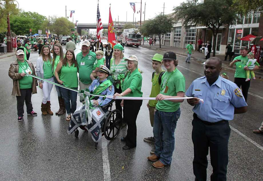 The 55th annual St. Patrick's parade Grand Marshall Houston Fire Captain William Dowling, center, his family and Houston Mayor Annise Parker pose for a photograph before the start of the parade Saturday, March 15, 2014, in Houston. Photo: James Nielsen, Houston Chronicle / © 2014  Houston Chronicle