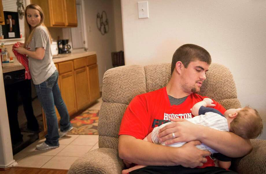 University of Houston football player Rowdy Harper, cradling 8-month-old son Jax, says even $2,000 more from the school would help him and his wife, Katie, make ends meet. Photo: Smiley N. Pool, Staff / © 2014  Houston Chronicle