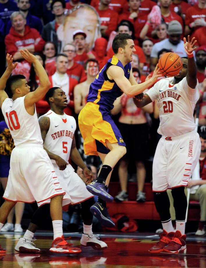 Albany's Peter Hooley (12) leaps into the air to pass the ball in front of Stony Brook's Carson Puriefoy (10), Dave Coley (5) and  Jameel Warney (20) during an NCAA college basketball game in the championship of the America East Conference tournament Saturday, March 15, 2014, in Stony Brook, N.Y. Hooley was awarded the MVP of the game during Albany's 69-60 win. (AP Photo/Kathy Kmonicek) ORG XMIT: NYKK117 Photo: Kathy Kmonicek / FR170189 AP
