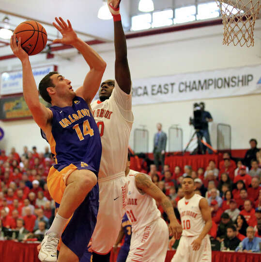 Albany's Sam Rowley drives the lane against Stony Brook's Jameel Warney in the America East Champion