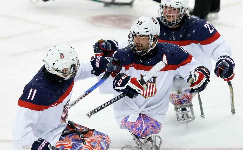 Rampage sled hockey player Josh Sweeney (center) is congratulated by Tyler Carron (left) after scoring what proved to be the game-winner for the U.S. Photo: Harry Engels / Getty Images / 2014 Getty Images