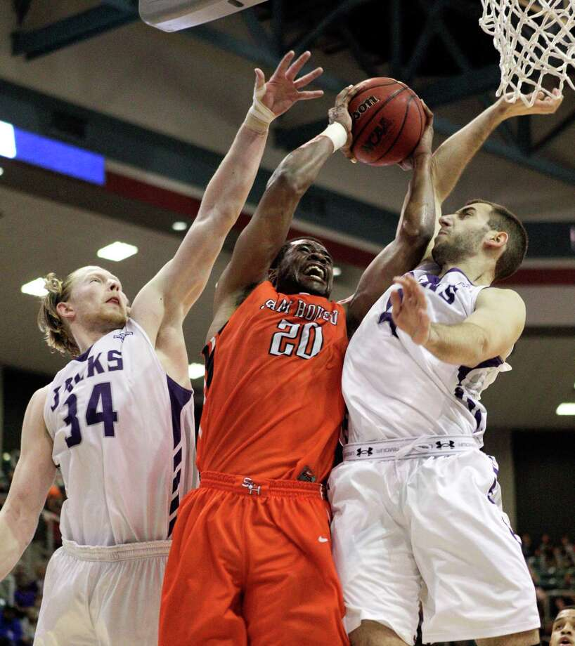 Sam Houston State's James Thomas (20) is fouled by Stephen F. Austin's Nikola Gajic (4) as  Jacob Parker (34) assists on the defense during the first half of an NCAA college basketball game in the championship of the Southland Conference tournament Saturday, March 15, 2014, in Katy, Texas. (AP Photo/Bob Levey) Photo: BOB LEVEY, Associated Press / FR156786 AP