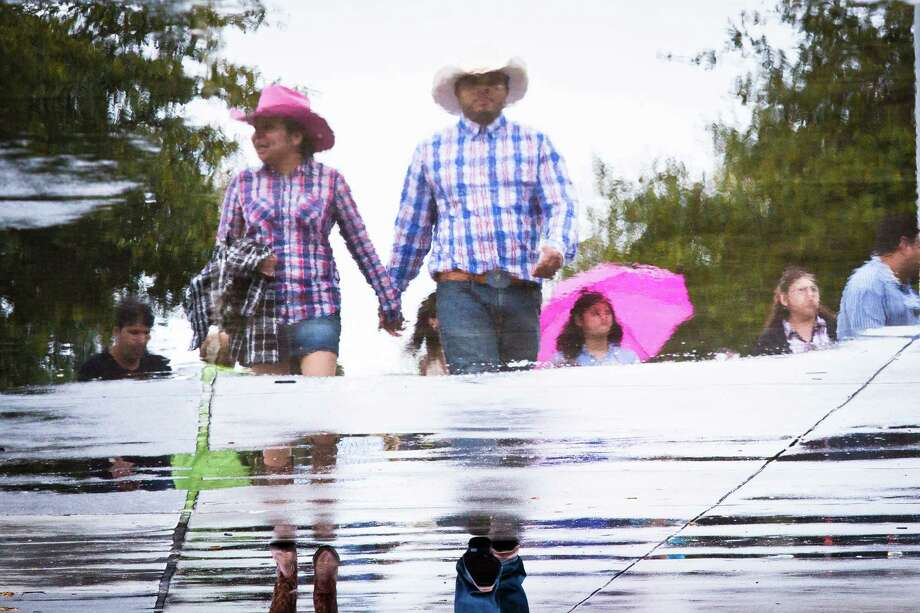 Sebastian Washington, 26,  and Guadalupe, 23, pass a puddle of water on their way to the entrance to Reliant Stadium to see the Rodeo Houston and the Hunter Hayes concert during a rainy afternoon, Saturday, March 15, 2014, in Houston. Photo: Marie D. De Jesús, Houston Chronicle / © 2014 Houston Chronicle