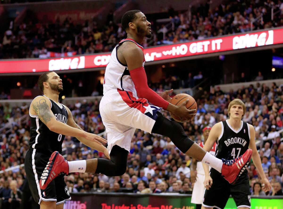 WASHINGTON, DC - MARCH 15: John Wall #2 of the Washington Wizards puts up a shot during the second half of the Wizards 101-94 win over the Brooklyn Nets at Verizon Center on March 15, 2014 in Washington, DC. NOTE TO USER: User expressly acknowledges and agrees that, by downloading and or using this photograph, User is consenting to the terms and conditions of the Getty Images License Agreement. (Photo by Rob Carr/Getty Images) ORG XMIT: 182422572