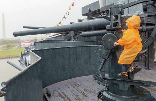 """Despite the driving rain, 6-year-old Brett Pinkston tries to take a bead on the distant San Jacinto Monument with a 3"""" cannon. Photo: Craig Hartley, For The Chronicle / Copyright: Craig H. Hartley"""