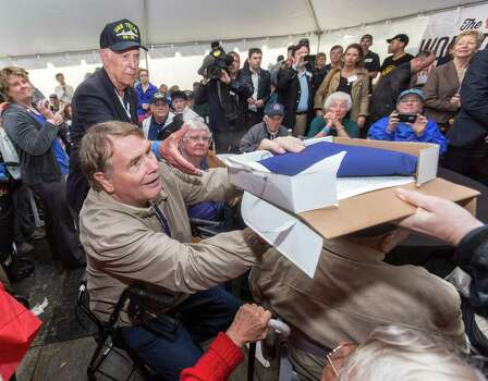 Thanks to the driving rain, the crew member ceremony had to be held in the limited shelter of the VIP tent. Here, Michael Jones passes over the flag that flew above the capitol to Orlan Scott, age 86, on his birthday. Photo: Craig Hartley, For The Chronicle / Copyright: Craig H. Hartley