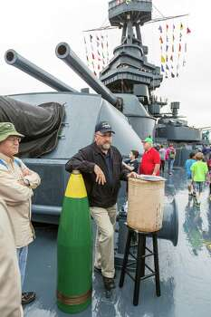 """John Hammond of the 1st Texas Volunteers explains to soggy onlookers how the 14"""" 1300-1500 pound shells worked with the 14""""/45 caliber naval rifles. Photo: Craig Hartley, For The Chronicle / Copyright: Craig H. Hartley"""