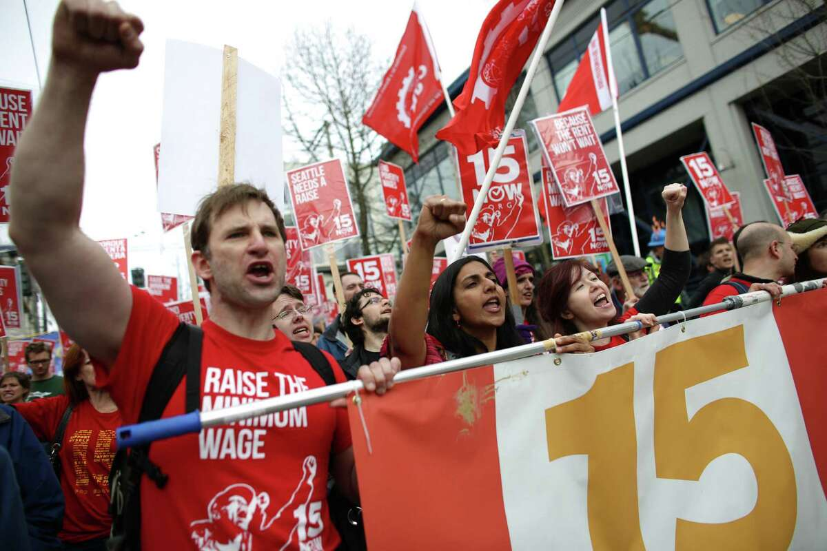 Organizer Bryan Watson, left, and Seattle City Councilmember Kshama Sawant lead the way during a march in Seattle to raise the minimum wage to $15 per hour. Hundreds of people marched from Judkins Park to Seattle Central Community College where a rally was held. Photographed on Saturday, March, 15.