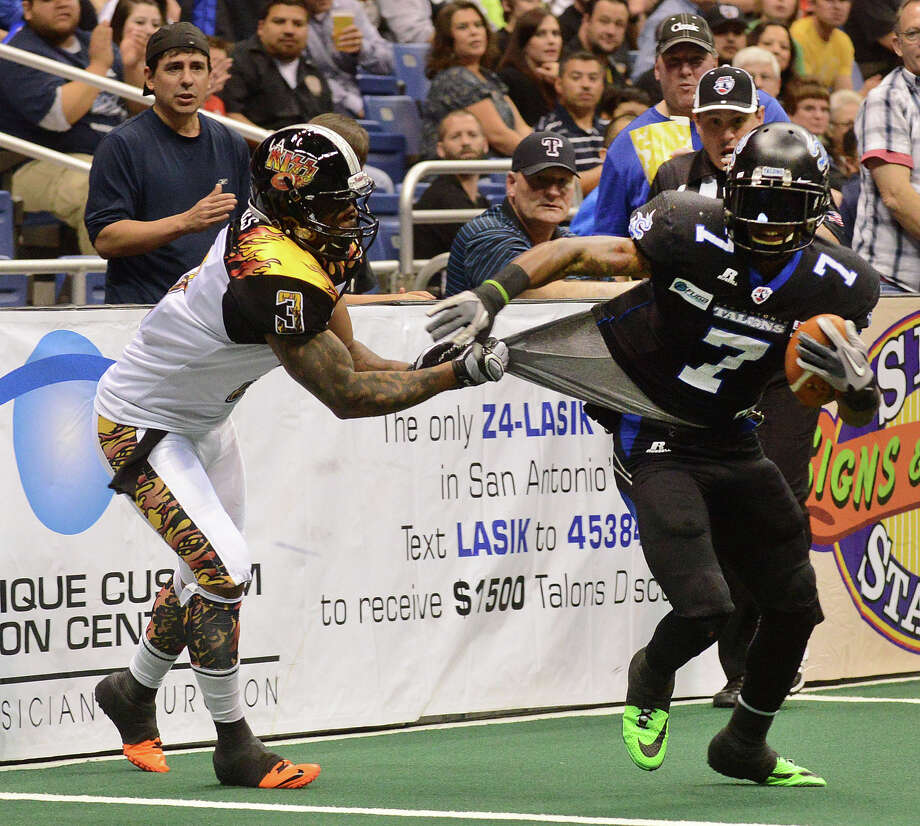 Receiver D.J. Stephens of the San Antonio Talons attempts to get away from Andre Jones of the Los Angeles KISS during Arena Football League action in the Alamodome on Saturday, March 15, 2014. Photo: Billy Calzada, San Antonio Express-News / © 2014 San Antonio Express-News