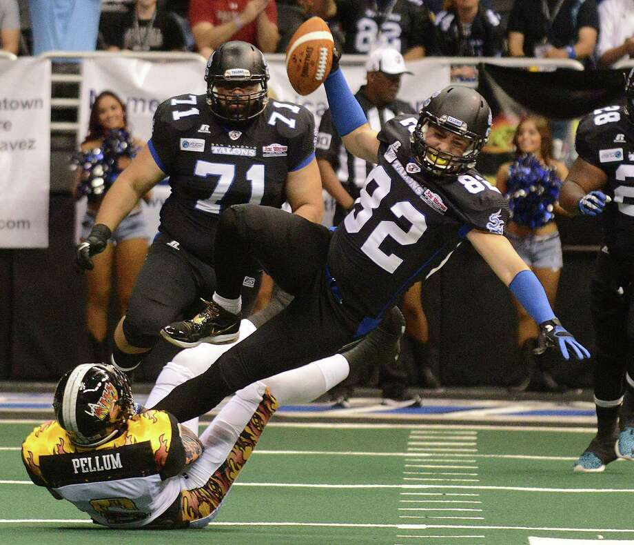 Receiver Robert Quiroga of the San Antonio Talons is upended by Romeo Pellum of the Los Angeles KISS after catching a pass during Arena Football League action in the Alamodome on Saturday, March 15, 2014. Photo: Billy Calzada, San Antonio Express-News / © 2014 San Antonio Express-News