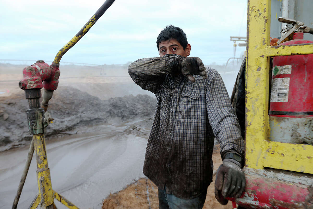 Derrickman Nestor Lerma, Jr. 36, of Freer, takes a quick break while mixing mud at a drilling site in Frio County, Monday, Jan. 21, 2013. The mud is used to build up the walls of the hole they are drilling.