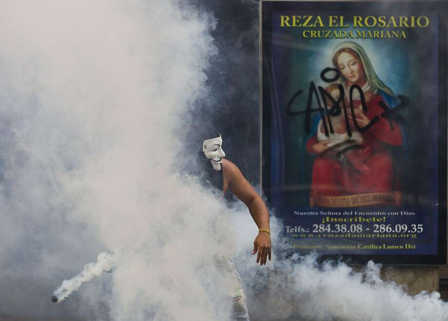 A protester wearing a Guy Fawkes mask, throws back a tear gas canister fired by Bolivarian National Police during clashes in Caracas, Venezuela, Saturday, March 15, 2014. Daily street protests and demonstrations continue in the capital and other cities. The Venezuelan government says at least 25 people have died in the turmoil since Feb. 12. (AP Photo/Esteban Felix) Photo: Esteban Felix, Associated Press