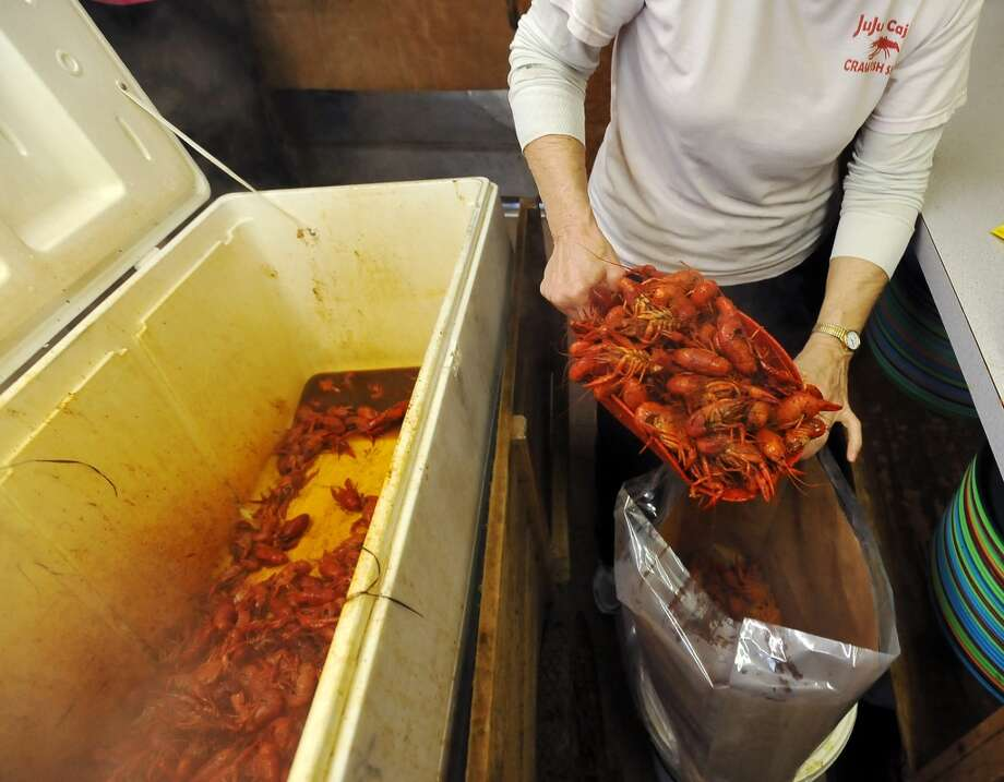 Mary Ferguson scoops up crawfish from an insulated cooler for a to-go order Thursday. JuJu's Cajun Crawfish in Fannett serves up nothing but crawfish, corn on the cob, and potatoes during the mudbug season. The small, family-owned restaurant is in its 12th year. Photo taken Thursday, 2/27/14 Jake Daniels/@JakeD_in_SETX