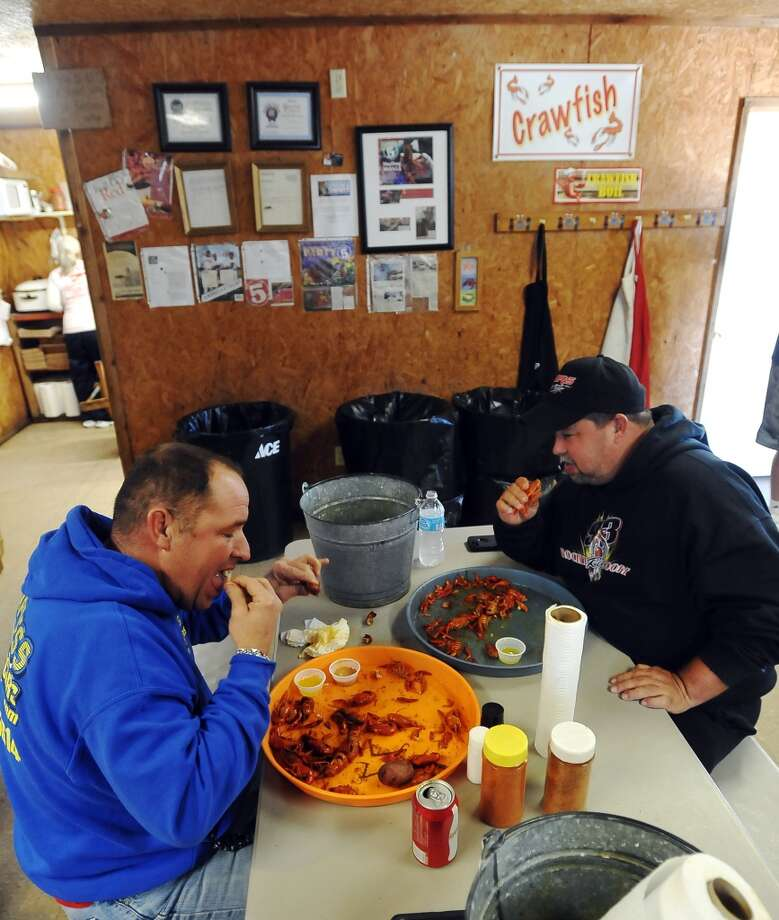 Michael Tanner, left, and Jason Foux finish off a few pounds of crawfish Thursday afternoon. JuJu's Cajun Crawfish in Fannett serves up nothing but crawfish, corn on the cob, and potatoes during the mudbug season. The small, family-owned restaurant is in its 12th year. Photo taken Thursday, 2/27/14 Jake Daniels/@JakeD_in_SETX
