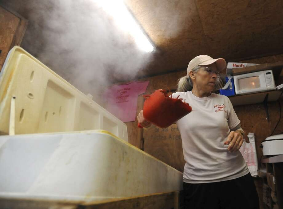 Mary Ferguson scoops some still steaming crawfish out of an insulated cooler Thursday afternoon. JuJu's Cajun Crawfish in Fannett serves up nothing but crawfish, corn on the cob, and potatoes during the mudbug season. The small, family-owned restaurant is in its 12th year. Photo taken Thursday, 2/27/14 Jake Daniels/@JakeD_in_SETX