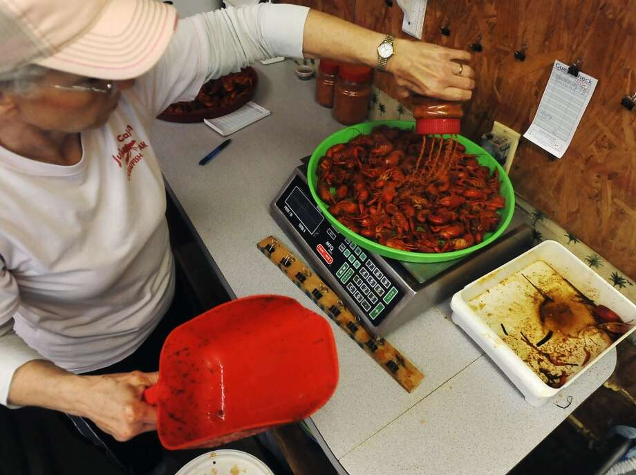 Mary Ferguson seasons up a few pounds of fresh crawfish Thursday afternoon. JuJu's Cajun Crawfish in Fannett serves up nothing but crawfish, corn on the cob, and potatoes during the mudbug season. The small, family-owned restaurant is in its 12th year. Photo taken Thursday, 2/27/14 Jake Daniels/@JakeD_in_SETX